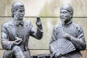 statues-representant-le-theme-de-lorient-rencontre-loccident-louest-du-19e-siecle-et-marchands-chinois-converser-autour-dun-the-d7eg25